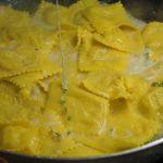 Scolare i ravioli e passarli in padella con la crema di formaggio